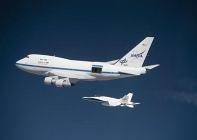 Courtesy NASA/Jim Ross<br> NASA's Stratospheric Observatory for Infrared Astronomy opens its  telescope cavity doors while a NASA F/A-18 mission support aircraft keeps pace during a test flight.