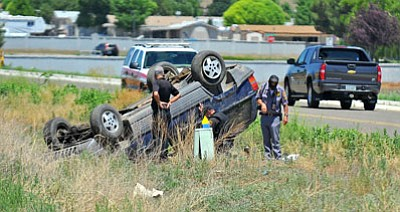 Matt Hinshaw/The Daily Courier<br> Prescott Valley Police Department officers and volunteers look over the scene of a single-vehicle rollover on Highway 69 near the intersection of Bradshaw Mountain Road Thursday afternoon.