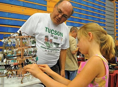 Matt Hinshaw/The Daily Courier<br> Jack Messersmith helps Kate Burk, 8, pick out a set of earrings at his booth during the 8th annual Prescott Gem and Mineral Show at Embry-Riddle Aeronautical University.