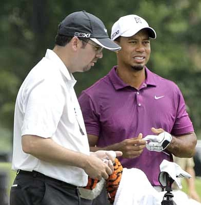 Amy Sancetta/The Associated Press<br>Tiger Woods and his caddie, Bryon Bell, stand at the driving range on Thursday, the day of the opening round of the Bridgestone Invitational golf tournament in Akron.