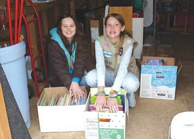 Courtesy photo<br>Sierra Cottle, left, and Leandra Benson White, right, Cadettes in Girl Scout Troop 713, stack some of the 200 early reader books they collected to donate to the Head Start program in Yarnell.