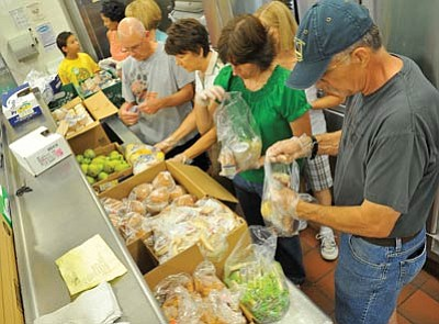 Matt Hinshaw/The Daily Courier<br>From left, Everett Sanborn, Kathy Eiskamp, Lorraine Tirrell and John Gage, volunteers with Prescott Area Leadership, put together sack lunches for students in the Hungry Kids Project Friday morning in Prescott. The project provides two breakfasts, lunches and dinners to 85 children in need in the Prescott Unified School District for their weekend.