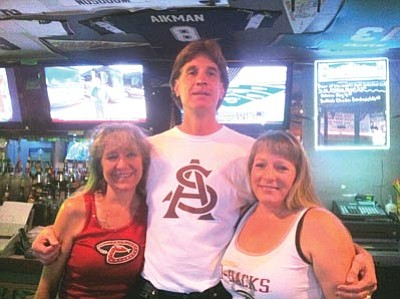 Peter Marx/The Daily Courier <br /><br /><!-- 1upcrlf2 -->The owner of Pudge & Asti's Sports Grill, Craig Denny, middle, stands behind the bar with his wife Suzy Denny, left, and bartender Monica Foard. The local bar was one of 12 establishments nominated as a finalist for ESPN Mobile Web's Best Sports Bars in North America contest.