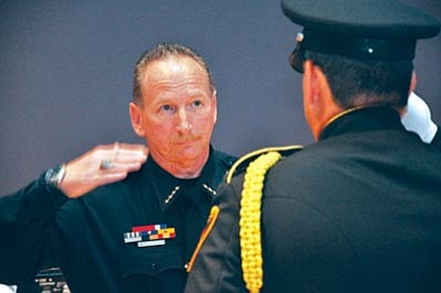 Heidi Dahms Foster/Courtesy photo<br>Newly sworn-in Prescott Valley Police Chief Bill Fessler salutes a member of the Police Honor Guard during a ceremony Thursday evening at the Prescott Valley Civic Center  auditorium.