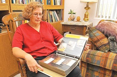 Matt Hinshaw/The Daily Courier<br> Amy Rea looks at a photo album of pictures she took of the New York skyline from her Jersey City apartment. Rea, who now lives in Prescott, was in New York City 10 years ago when the World Trade Center towers fell.