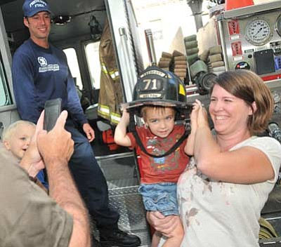 Les Stukenberg/The Daily Courier<br>Prescott Fire Captain Brian Murphy and Jamie Winslow look on as Zachary Winslow gets his picture taken with a Prescott Fire Department helmet before the 9/11 Tenth Anniversary Commemoration on the Yavapai County Courthouse Plaza Sunday evening.