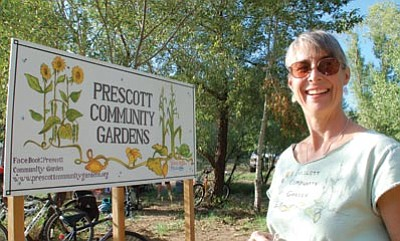 Cindy Barks/The Daily Courier<br> Prescott Community Gardens President Colleen Sorensen stands in front of the sign for the new Granite Creek Park-area garden, which is set to open on Oct. 15.