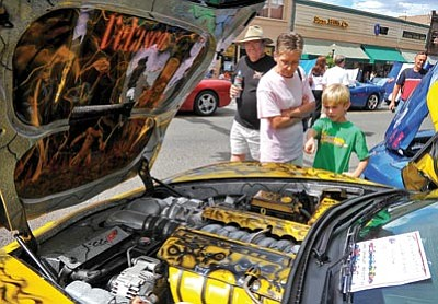 Matt Hinshaw/The Daily Courier<br> Tanner Bond, 7, and his grandmother Patricia Wright check out the engine of a 2006 C6 custom Chevrolet Corvette.