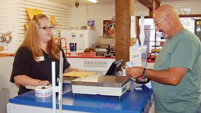 Jason Soifer/The Daily Courier<br>Amanda Burns, assistant manager at the Twin Lakes Market, helps Ed Santiago mail a package.