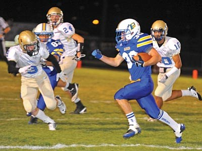 Matt Hinshaw/The Daily Courier<br /><br /><!-- 1upcrlf2 -->Prescott High's Dakoda Peterson runs past Sandra Day O'Connor's Brandon Brown (10) and Daniel Turski (3) Friday night in Prescott. The Badgers are 2-4 on the season and have lost two consecutive games by six points or less.