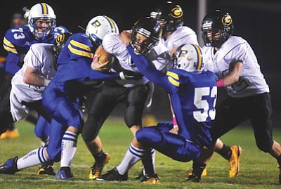 Photos by Les Stukenberg/The Daily Courier<br /><br /><!-- 1upcrlf2 -->A pair of Prescott High defenders take down quarterback Kaler Ray during the Badgers' homecoming game against Barry Goldwater Friday night in Prescott. The Badgers beat the Bulldogs, 20-7.