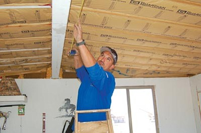 Jason Soifer/The Daily Courier<br> Ricky Loftin prepares to install a ceiling light at his Paulden home earlier this week. Loftin bought the 1,700-square-foot home on nearly 6 acres for $75,000.