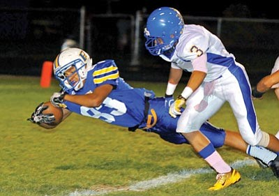 Photos by Matt Hinshaw/The Daily Courier<br /><br /><!-- 1upcrlf2 -->Prescott High's Kaine Bayze dives into the endzone, scoring the Badgers' third touchdown of the game in the first quarter, while Kingman High School's Gabe Lumas looks on Friday night in Prescott.