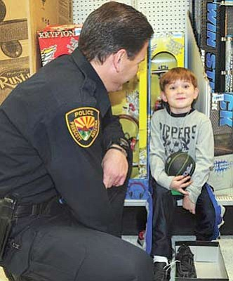 Brett Soldwedel/The Daily Courier<br>Ethan, 7, is excited to shop with Prescott Police Officer Matt Medina at Kmart in Prescott Valley during last year's Shop with a Cop event.