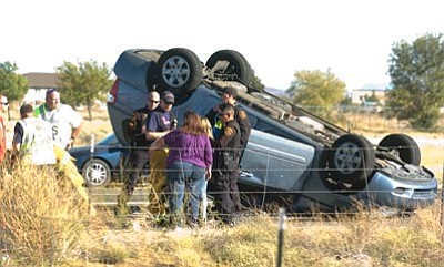 Les Stukenberg/The Daily Courier<br> Emergency personnel treat the two occupants of this rollover near the intersection of Lakeshore Drive and Civic Center in Prescott Valley Thursday afternoon.
