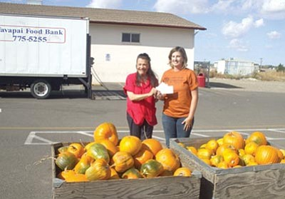 Courtesy photo<br>Sharla Mortimer, owner of Mortimer Family Farms, presents 300 pumpkins and a $700 check to Ann Wilson, executive director of the Yavapai County Food Bank.