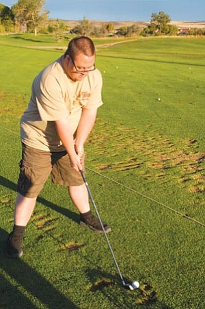 Cindy Barks/The Daily Courier<br>Justin Jaeger, a player on the local Special Olympics golf team, lines up a shot during a recent practice at the Antelope Hills Golf Course.