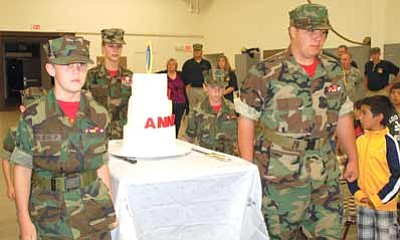 Lisa Irish/The Daily Courier<br>Central Arizona Young Marines Pfc. Paul Kinach, left, Lance Cpl. Ian Watson, back left, Staff Sgt. Brittany Carr, center, Pvt. Caleb Stober, back right, and Pfc. Dominic Lindquist front right carry their 10th anniversary cake during their ceremony on Oct. 17 at the National Guard Armory in Prescott.