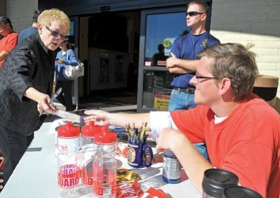 Matt Hinshaw/The Daily Courier<br> Flo Kik hands Danny Wrigley a donation for the Special Olympics as NARTA student Adam Mastalski looks on Saturday in front of the Prescott Valley Safeway during the annual Cop on Top event.