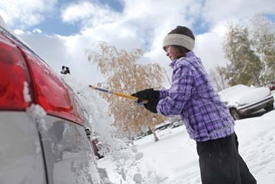 Jake Bacon/The Associated Press<br> Iris Dixon, 9, cleans her mother's car Saturday in Flagstaff. Flagstaff received  5.6 inches of snow overnight during the first major snowstorm of the  season. About 2 inches of snow fell in parts of Prescott.