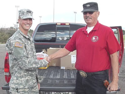 Courtesy photo<br>Murrell Worth, right, shakes hands Oct. 25 with Cadet Capt. Albert Schwartz, who led Embry-Riddle Aeronautical University's Army ROTC's collection of food and personal care items to be sent to troops around the world.