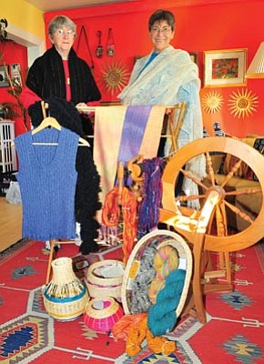 Les Stukenberg/The Daily Courier<br> Jeanne Zinda and Yvonne Johnson show off some of the items that will be available at the Mountain Spinners and Weavers annual show and sale Saturday.