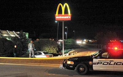 Matt Hinshaw/The Daily Courier<br> Prescott Valley police officers and detectives survey the scene in front of McDonald's after an alleged carjacking that started on Gurley Street in Prescott.