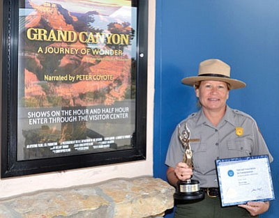 Grand Canyon Chief of Interpretation and Resource Education Judy Hellmich-Bryan holds park Aurora and NAI Awards. Michael Quinn/NPS