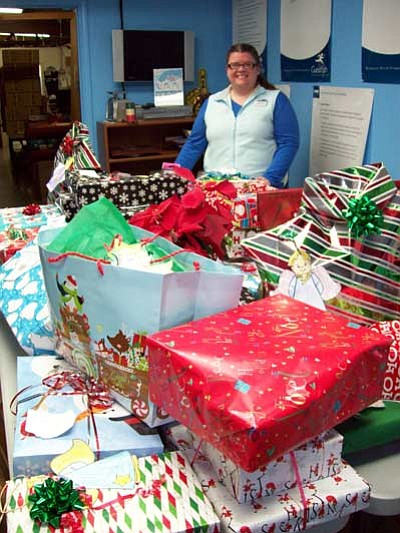 Delaware North Assistant Store Manager Carrie Putz stands with angel gifts ready for distribution after last year's wrapping party. Submitted Photo <br /><br /><!-- 1upcrlf2 -->