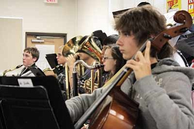 From foreground, Zach Tacey plays the cello, Josephina Legaspi plays bass clarinet, John Morfin rests on his baritone, and Alex Thompson and Nathan Lenz wait for their cue on tenor sax. Clara Beard/WGCN<br /><br /><!-- 1upcrlf2 -->