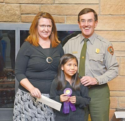 """Red Feather Inn's Julie Aldaz and Grand Canyon National Park Superintendent Dave Uberuaga present Ceres Tisi with Best in Show for her oil painting called """"Home"""" during the Arts in our Parks student exhibit opening inside Park Headquarters March 2."""