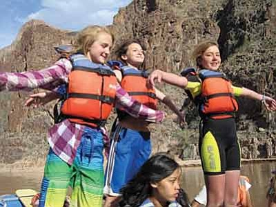 """Three Grand Canyon Middle School students """"take flight"""" while rafting down the Colorado River during a four day Grand Canyon Youth trip to the inner rim. Submitted Photo"""