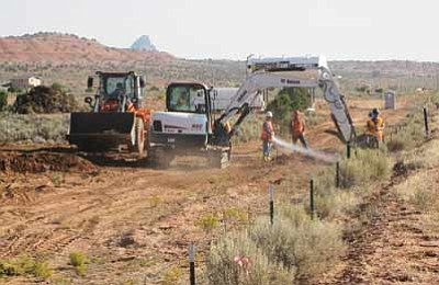 Workers hose down the Cove, Ariz. uranium clean up site to keep dust down. The process of cleaning up the Cove uranium transfer station involved digging up and hauling away tainted soil. Photo/U.S. Environmental Protection Agency