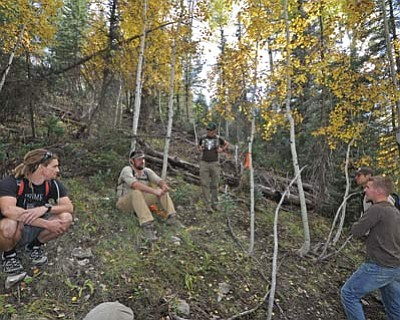 Volunteers listen to trail building organizers. Last year, about 25 cycling enthusiasts gathered along the Rainbow Rim Trail the weekend of Sept. 28-29 to learn about sustainable trail design from trainers with the International Mountain Bicycling Association. Photo/USDA Forest Service, Southwestern Region, Kaibab National Forest.<br /><br /><!-- 1upcrlf2 -->