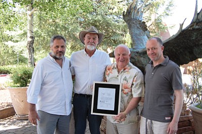 Stilo representatives Vittorio Bianchi and Federico Pellicioli present a framed copy of a 20-acre deed of property at Kotzin Ranch to Town of Tusayan Mayor Greg Bryan and Council Member John Rueter June 5. The land was donated to the town as part of a revised development agreement approved by the council in March. Another 20-acre deed donated by Stilo to the town is in escrow pending approval of a road easement application being reviewed by the Kaibab National Forest. Submitted photo