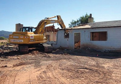 A backhoe demolishes a building on the Navajo Nation that was contaminated by radiation exposure from abandoned uranium mines. The EPA reported that during the five-year plan it demolished 38 buildings because they were contaminated. Photo/Environmental Protection Agency