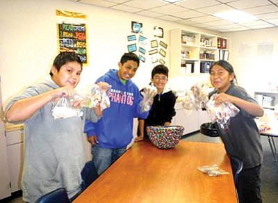 Seventh graders Malik Ali, Mauricio Torres Gonzales, Roberto Saavedra and Rufus Keebahe hold bags of boxtop labels. Photo/Lori Rommel