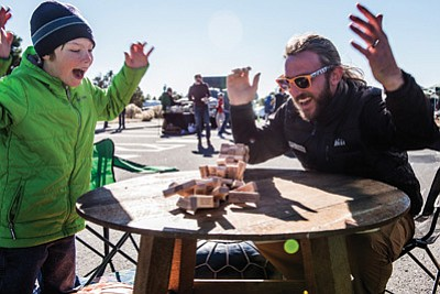 REI Flagstaff Market Coordinator Justin Inglis plays Jenga with a young visitor to the REI Village. Photo/Terri Attridge