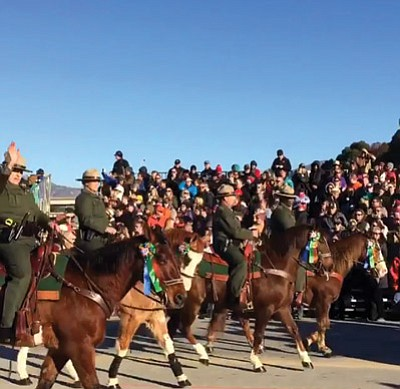 Grand Canon NPS equestrian unit waves to crowds lining the parade route. Photo/NPS Instagram