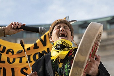 Klee Benally of the Navajo Nation sings as part of a protest outside the EPA over pollution from uranium mines. Photo/Danika Worthington, Cronkite News