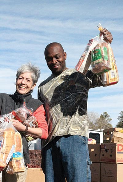 Tony Jordan and Emilee Davis help hand out bread and load vehicles with St. Mary's Food Boxes Feb. 17. Loretta Yerian/WGCN