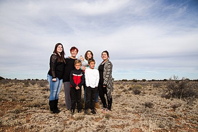 Sue Winchester (center) with her adopted and foster children stand on their property in Valle, Arizona where Bella's Place will be built. From left: Jessica Ross-Mentor, Gunner, Kaylee and Alexus. Front: Seven-year-old twins Matthew and Gary Bond. Ryan Williams/WGCN