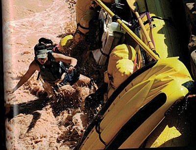 A raft flips over on Bedrock Rapid at river mile 130 of the Colorado River. Tom Myers new book 'Flipped Out' celebrates rafting culture and photos from river trips. Photo/Matt Fahey/'Flipped Out'