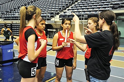 From left: Savannah Perkins, Monica Dimas, Candy Lopez and Meaghan Donehoo listen as Coach Elna Perkins instructs the girls before the 4 x 400 relay. Photo/Cyndi Moreno