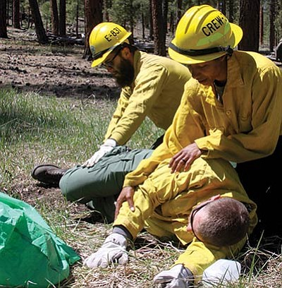A crewmember creates an incident within an incident during a simulated fire shelter deployment on the North Kaibab readiness review training May 12. Photo/David Hercher, KNF