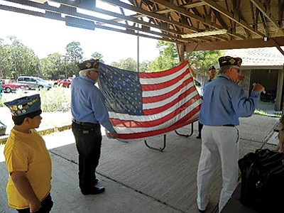 John Ivens Post 42 explains the meaning behind each fold of the flag to students at Kaibab Learning Center. Photo/Scott Miller
