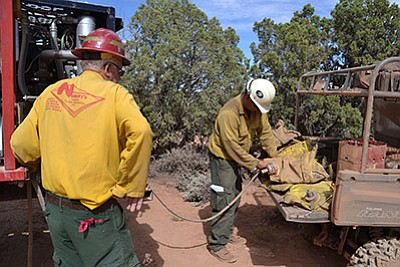 firefighters filling up bladder bags with water for mopping up the fire. Photos/courtesy of Kaibab National Forest, U.S. Forest Service