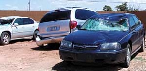 Above. three elk-damaged vehicles at a local tow yard. Below, a flashing warning sign on a project near Payson.