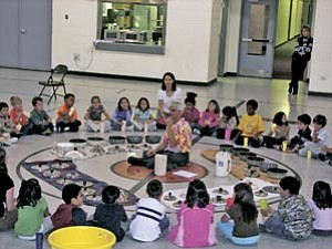 First graders circle around artist in residence Step Raptis and the items they'll use to create a musical performance.