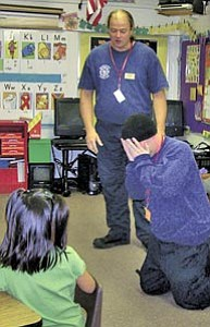 "Under the direction of Capt. Greg Brush, Jason ""Junior"" Rowley of Xanterra Fire and Safety shows how to protect from flames during a recent program at Grand Canyon School for Fire Prevention Week."